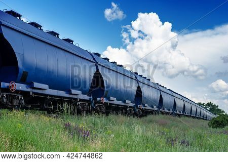 Industry, Logistics, Transportation Concept. Moving Train With Grain Wagons On The Background Of The