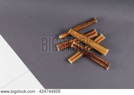 Pet Treats. A Group Of Brown Treats On A Gray And White Background. 5-inch Bully Sticks. Beef Pizzle