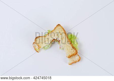 Uneaten Tuna Sandwich On A White Background. Half-eaten Sandwich With Fish, Red Tomatoes, Green Lett