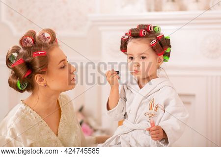 Adorable Little Girl With Her Mother In Hair Curlers Apply Makeup. Mom Teaches Daughter To Use Cosme
