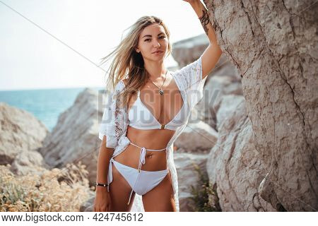 Beautiful Woman Near The Cliff On The Sea Coast In A White Swimsuit And Tunic