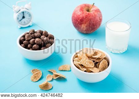 Bowls With Cereal And Chocolate Balls, A Glass Of Milk, An Apple And An Alarm Clock On A Blue Backgr