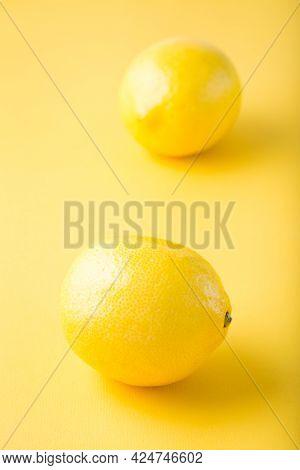 Two Ripe Whole Lemons On A Yellow Background. Detox Fruit Diet, Body Detoxification. Vertical View