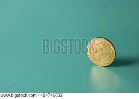 Bitcoin Crypto Gold Single Coin On Green Teal Backround With Copy Space. Popular Cryptocurrency Bann