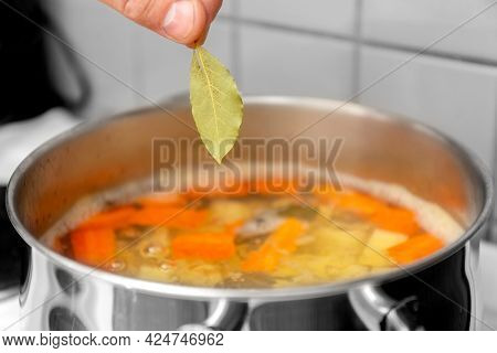 The Chef Cooks Finnish Salmon Soup. The Cook Puts A Bay Leaf In A Saucepan. High Quality Photo