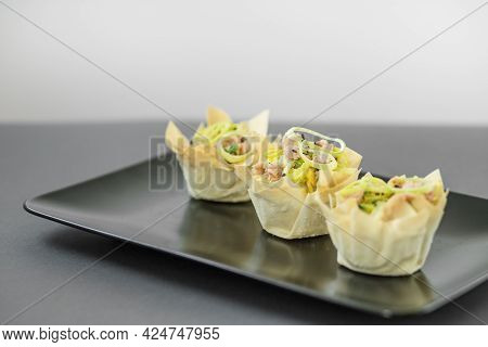 Three Tartlets With Tuna And Onions On A Black Plate, Buffet Appetizer For Buffets. Beautifully Deco