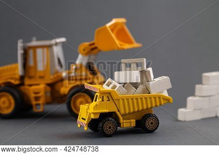 Yellow Dump Truck, Excavator, Building Materials. Cargo Track, Aerated Concrete Blocks. Delivery Bui