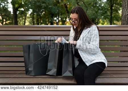 Woman Sits On Bench And Looks Into Shopping Bags. Tiresome Shopping. Black Friday Shopping, Discount