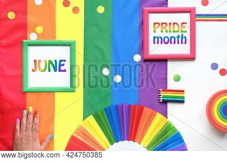 Rainbow Lgbt Flag Background With Frames, Fan, Pencils And Ribbons. Hand With Painted Nails.text Jun