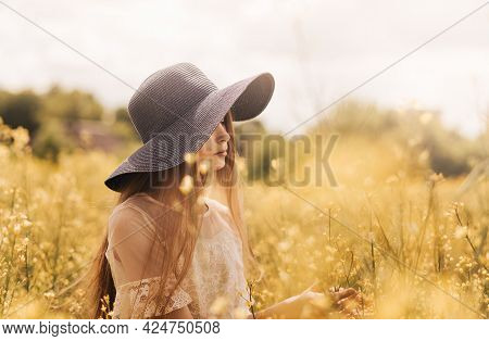 A Young Girl In A Hat Walks On A Rapeseed Field.