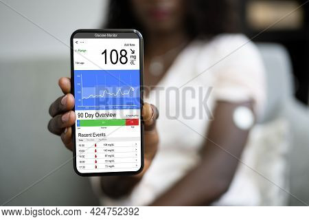 African Woman Using Continuous Glucose Remote Monitor Diabetes Sensor