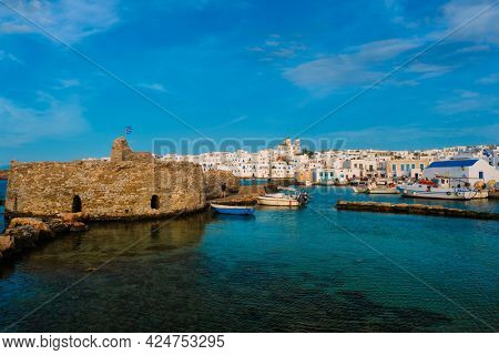 Picturesque view of Naousa town in famous tourist attraction Paros island, Greece with traditional whitewashed houses and small venetian castle fort