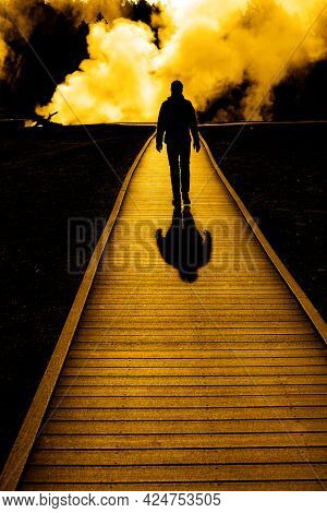 Silhouette of a single tourist walking on boardwalk with steam rising