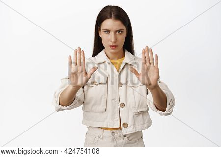 Stop. Serious And Confident Brunette Woman Raising Hands In Taboo Sign, Furrow Eyebrows, Give Warnin