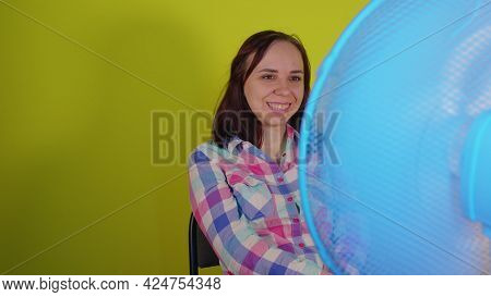 Close Up Of Young Woman Sitting On Chair In Front Of Fan On Yellow Background. Happy Brunette Laughi
