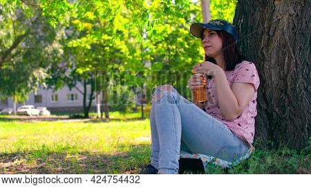 Young Woman Rests And Drinks Apple Juice, Sitting Near Tree On Street. Brunette In Cap Drinking Cool