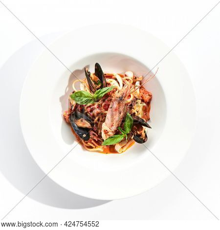 Seafood spaghetti pasta - spaghetti plate with seafood mix. Pasta dish with shrimp, mussel and octopus. Restaurant gourmet seafood and pasta food plate isolated on white background.