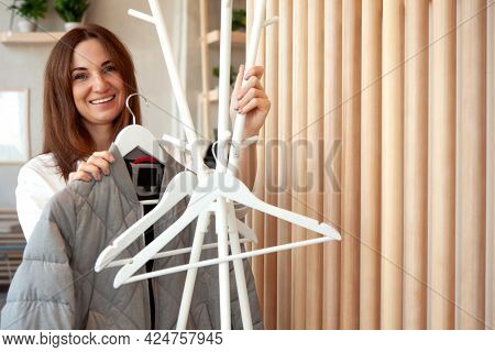 Beautiful Young Woman Hanging Empty White Hanger On White Stylish Clothes Rack With Hangers