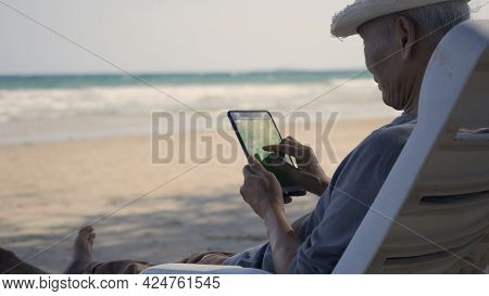 Senior Man Sitting On Chairs Enjoying Time On Beach Travel Vacation Using Tablet Computer, Romantic