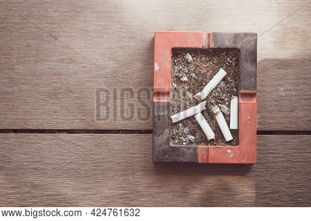 Ashtray With Cigarettes Butts On Wood Table