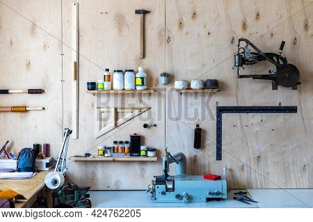 Wooden Wall At Leather Workshop. Different Tools And Equipment For Handcraft Working Tanner
