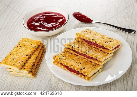 Bowl With Cherry Jam, Teaspoon With Jam, Few Cookies, Sandwiches From Crackers With Flax Seeds And J