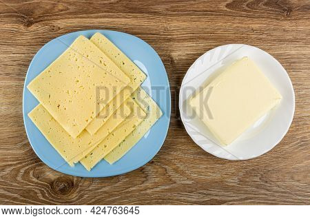 Few Thin Slices Of Cheese In Light-blue Glass Plate, Piece Of Butter In White Plate On Wooden Table.