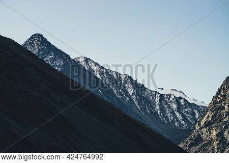 Beautiful Mountain Landscape With Black Peaked Top With White Snow Under Blue Sky. Snow-covered Poin