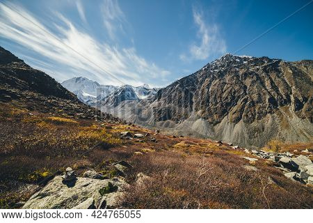 Autumn Sunny Landscape With Highland Valley And Snow-covered High Mountains Under Blue Cloudy Sky Wi