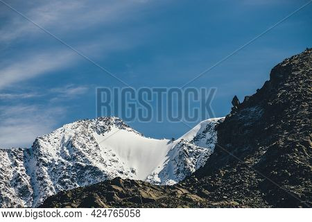 Awesome Alpine Landscape With Dark Rockies And High Snow-covered Mountains In Sunshine Under Blue Sk
