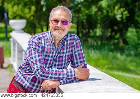 Relaxed Pensioner with Casual Clothing and Glasses in Park Smiling