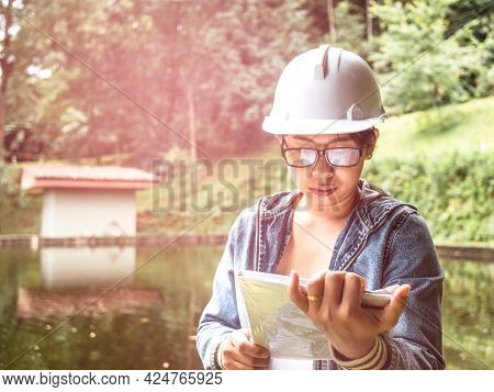 Female Ecologist In Safety Hat Working On Site At The Dam And Stands Reading The Blueprints At The C