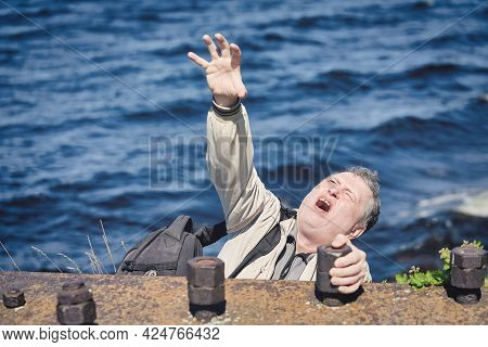 Freak Clings His Hands To The Edge Of The Cliff Above The Water