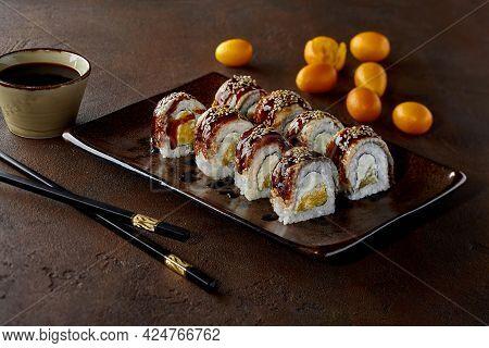 Sushi Rolls With Eel, Cream Cheese, Orange, Unagi Sauce And Sesame