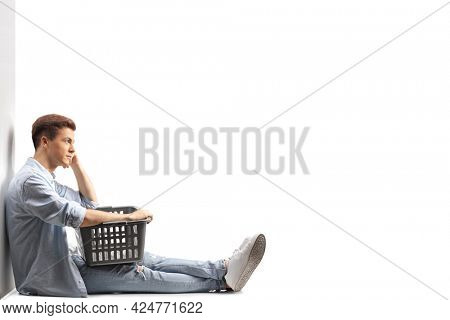Guy sitting and leaning on a wall with a laundry basket isolated on white background