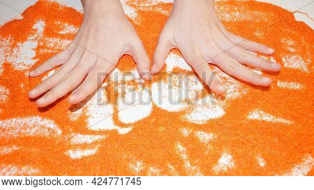 Hands Of A Teenager On Orange Kinetic Sand Sand Therapy For Autism.