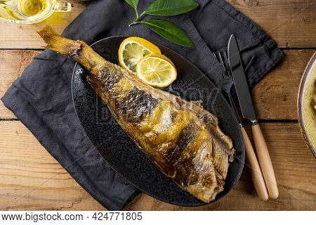 Baked Sea Bass Or Lingcod Fish On A Black Plate And Old Wooden Background Top View, Copy Space For T