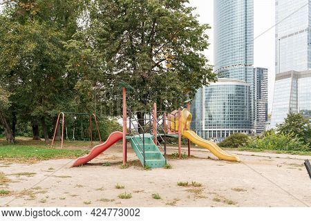Weird Worn-out Children's Playground Against The Backdrop Of Modern Skyscrapers.
