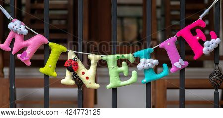 3d Plush Letters Name Banner For A Birthday Party, Decoration Hanging In A White Wall.