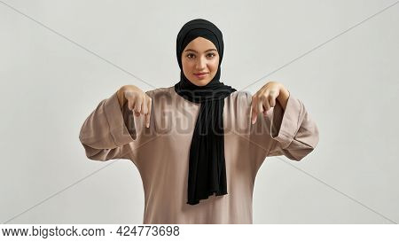 Happy Young Arabian Woman In Hijab Pointing Fingers Down While Looking At Camera On Light Background