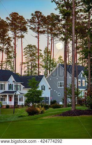 Full moon rising at sunset over beautiful suburban houses