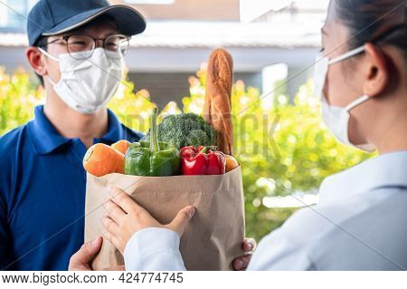 Woman Customer In Medical Face Mask Standing At The House To Accepting A Grocery Bag Of Food, Fruit,