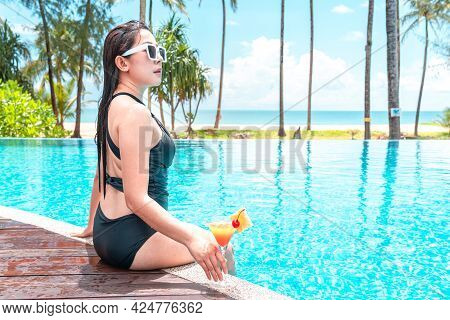 Asian Traveler Woman In Sunglass To Holding Cocktail And Sitting In A Swimming Poolside To Relaxing