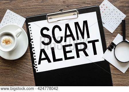 Scam Aler. Text On Wood Table, On White Paper