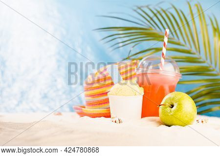 Tropical Rest On Exotic Sea Beach With Cold Drink, Ice Cream, Apple, Sun Hat, Palm Leaves With Sunli