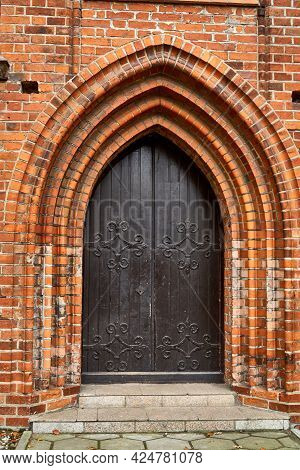 A Gate In An Orange Brick Building. Gothic Architectural Building. An Old House With An Iron Gate To