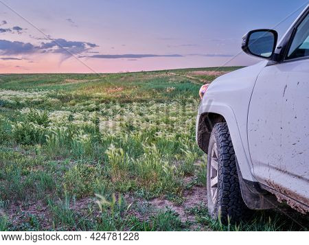 muddy SUV car or truck is riding at dusk through a green prairie - Pawnee National Grassland in northern Colorado, early summer scenery with wildflowers.