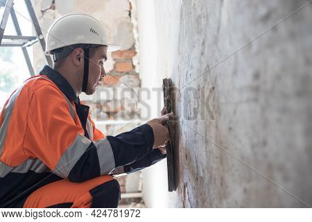 A Man In A Hard Hat And Work Clothes Is Making Repairs In An Apartment Room. Finishing Works. Profes