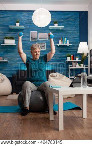 Senior Woman In Retirement Raising Hands Doing Arms Exercise Using Dumbbells Sitting Fitball Trainin