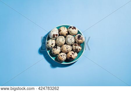 Top View - Quail Eggs And Green Small Plate On Pastel Blue Background. Minimal Happy Easter Composit